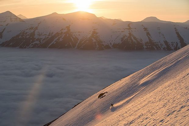 A wide shot shows a mountainous landscape with someone skiing down, low sun behind.
