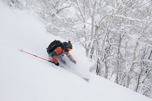 A skier in orange snowsuit and woolly hat sends up a cloud of snow as he travels down a slope by some trees.