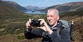 Outdoor photographer Alan Rowan stands on top of a hill in front of a lake and fields, holding a compact Canon camera.