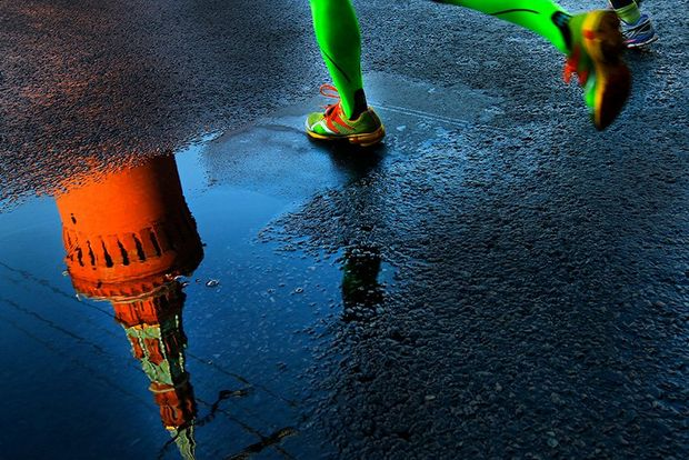 A tower of the Kremlin reflected in a puddle as a runner with bright green socks runs past. Photo by Andrey Golovanov.