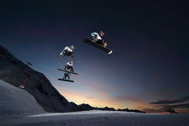 Three skiers captured in mid-air against a sunset sky.