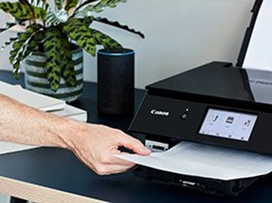 A user takes a printout from a black Canon printer, which has an Amazon Echo smart speaker next to it.
