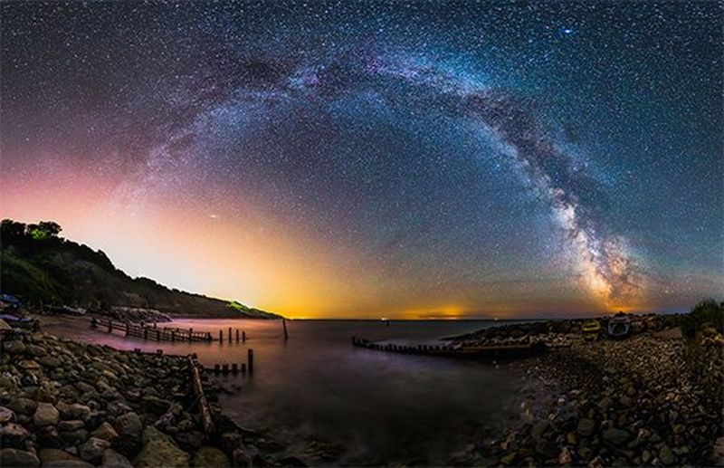 The milky way is seen forming an arch shape over the sea.