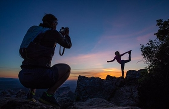 A man squats to photograph a woman standing on one leg, both silhouetted against a sunset.
