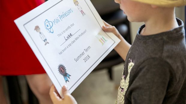 A child holds a Mini Professors certificate with his name on.