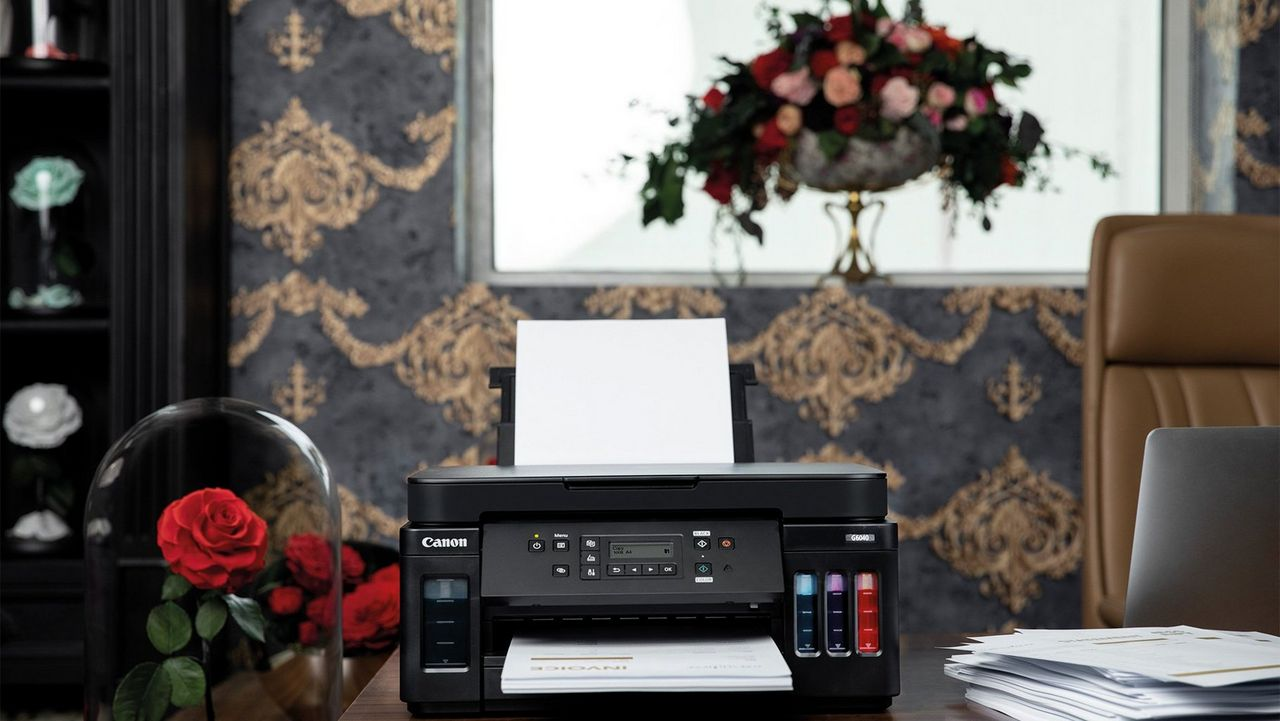 A desk with a Canon PIXMA G6040 and papers on top, next to a glass dome housing for a red rose.