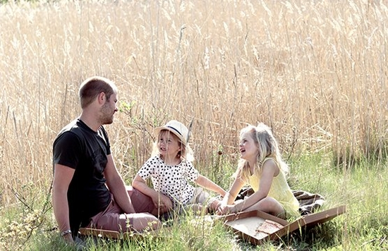 A man and two children sit in a sunny field enjoying a picnic. Photo by Hannah Clark on a Canon EOS 250D.