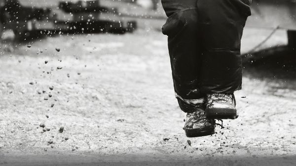 A black and white shot of someone splashing in puddles, photographed by Hannah Clark on a Canon EOS 250D.