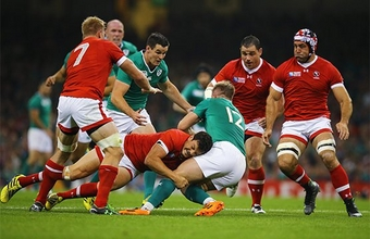 A Canadian player tackles an Irish player during a rugby match. Photo by Richard Heathcote.