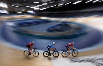 Three cyclists speed along an indoor cycle track.