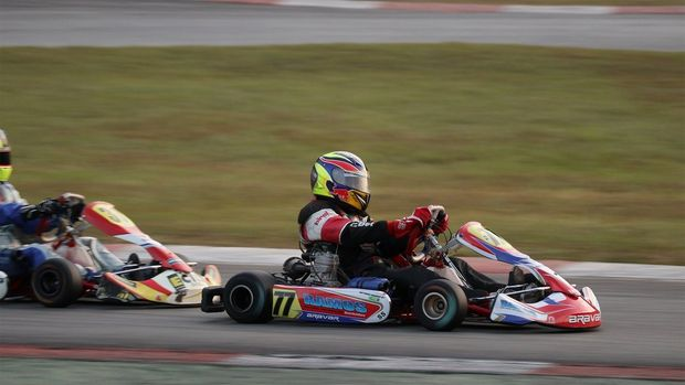 Two go-karts racing on a track; the front one is in sharp focus, with everything else blurred.
