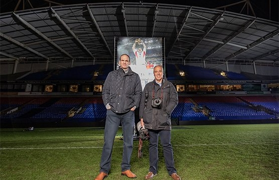 Sports photographer Dave Rogers stands next to rugby player Martin Johnson on the pitch.