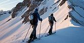 Two cross-country skiers makes their way up a mountain in low sunlight.
