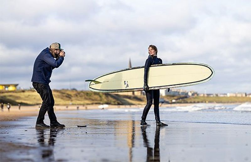Photographer Tom Bing on a beach taking a picture of a surfer holding her board.