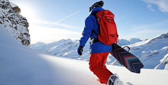 A snowboarder walks through the snow with his snowboard under his arm, away from the camera.