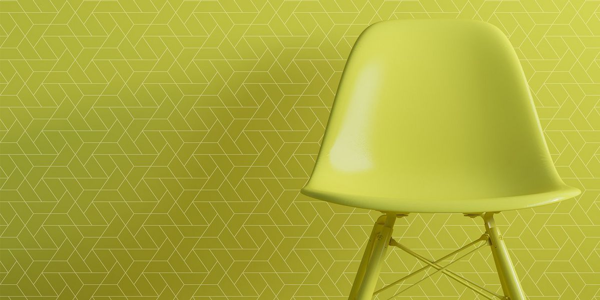 A green chair in front of digitally printed green wallpaper