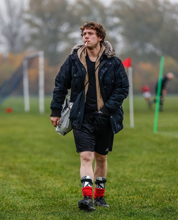 An amateur football player walking away from the pitch, smoking a cigarette.