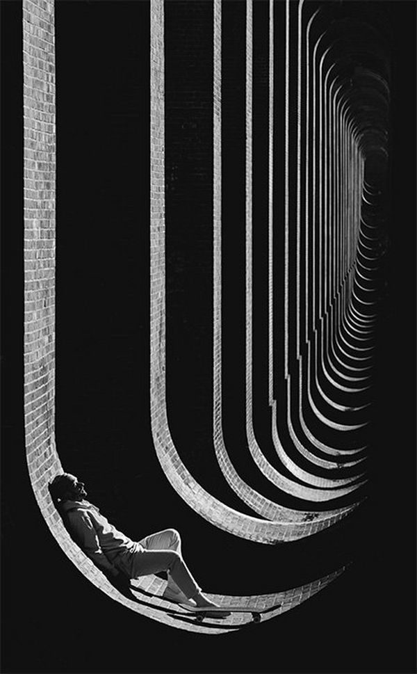 A skateboarder leans against the curved wall of a viaduct base. Photo by Lorenz Holder using a Canon EF 70-200mm f/2.8L IS II USM lens.