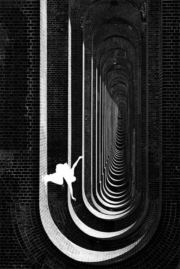 A black and white image shows underneath the viaduct, with a white silhouette figure skateboarding down one side of a wall.