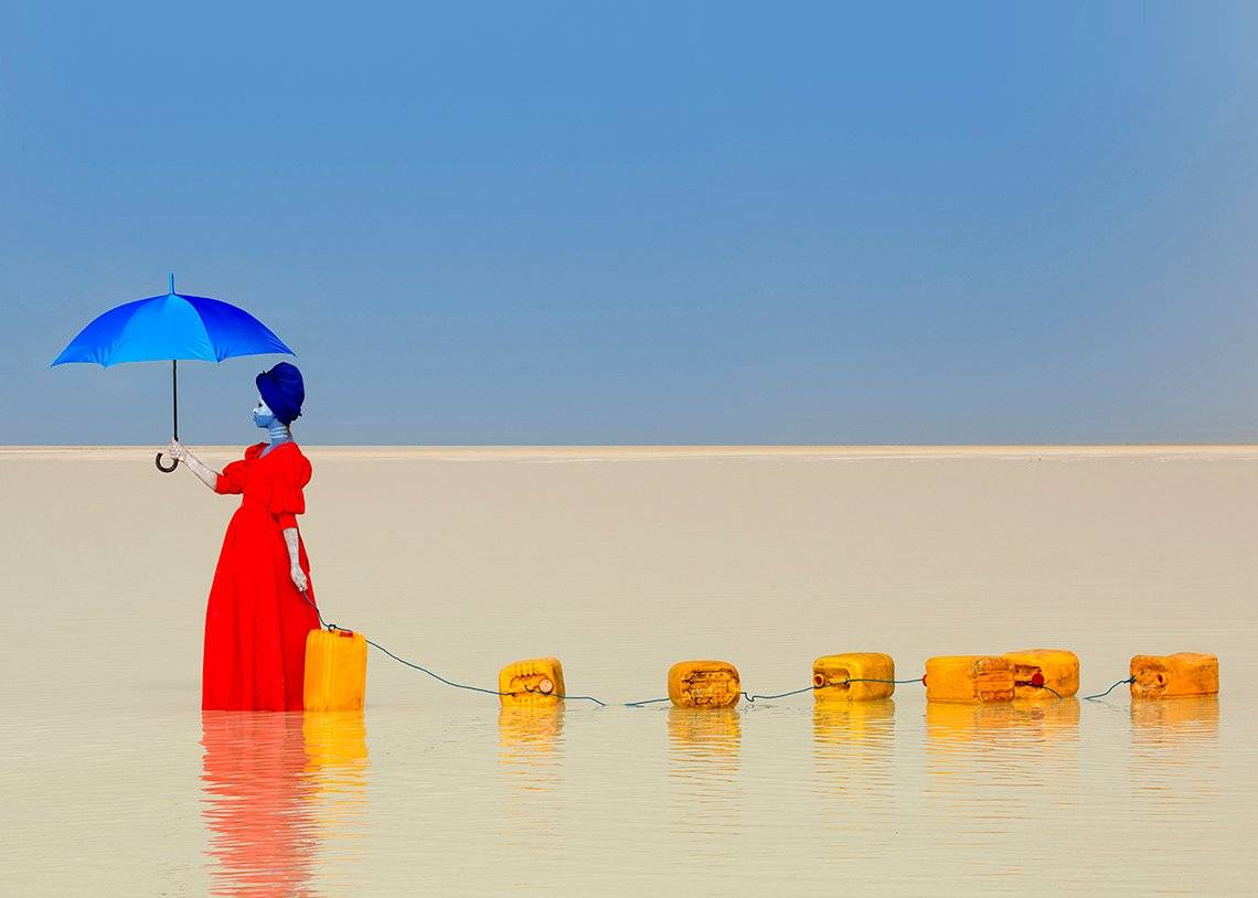 A woman in a red dress and holding a blue umbrella walks through shallow water dragging a chain of jerry cans behind her.