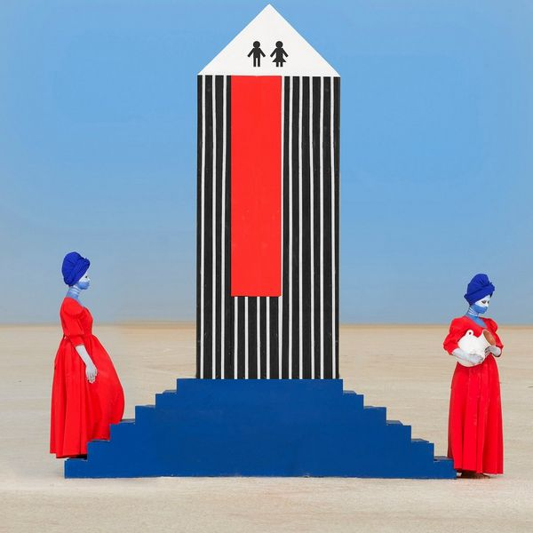 Two women in red dresses and wearing blue headscarves stand either side of a set of blue steps with a black-and-white striped structure on it.