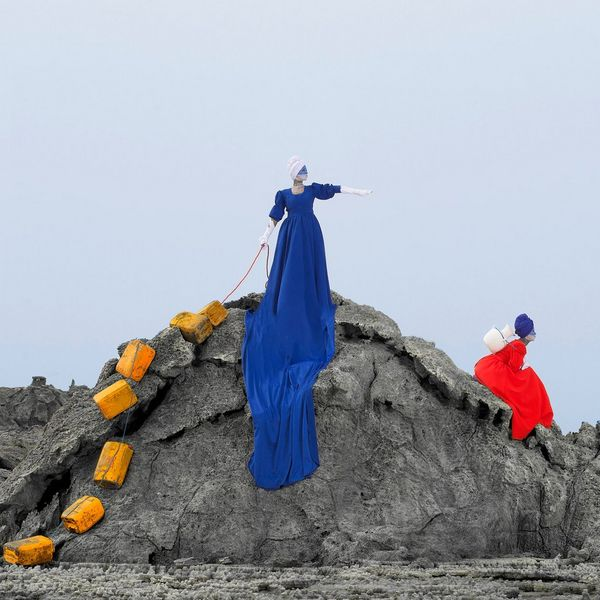 A woman in a long blue dress stands on a rock with a chain of jerry cans behind her. Another woman in a red dress sits on the side of the rock.