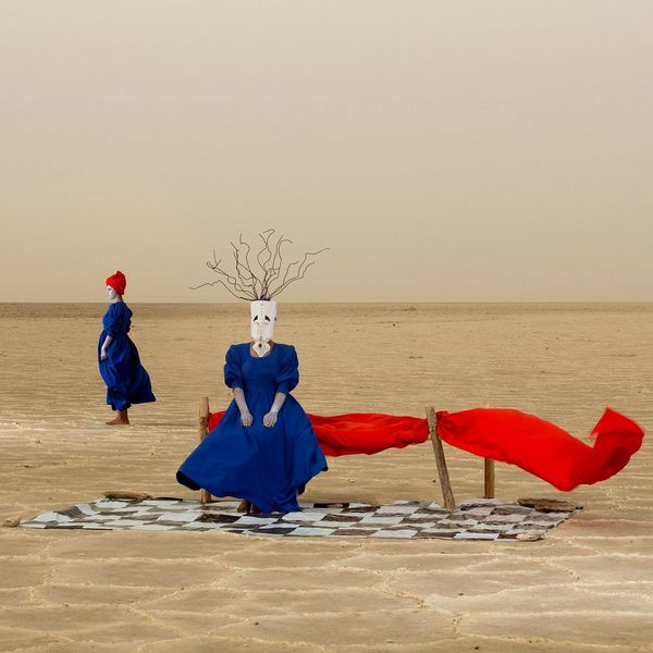 A woman in a blue dress sits on a red bench in the desert wearing a mask made from a jerry can. Another woman stands in the background.