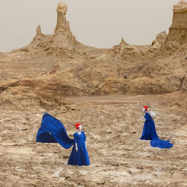Two women in blue dresses with flowing trains stand in a desert landscape.