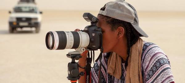 Canon Ambassador Aïda Muluneh looks through the lens of a Canon EOS 5D Mark IV on a tripod.