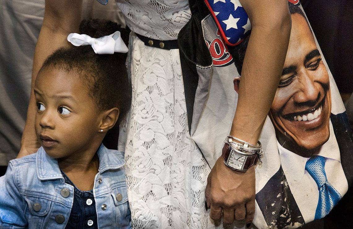 A girl is looking away from her mother, who wears a large Obama bag over her shoulder, which features an image of the President.