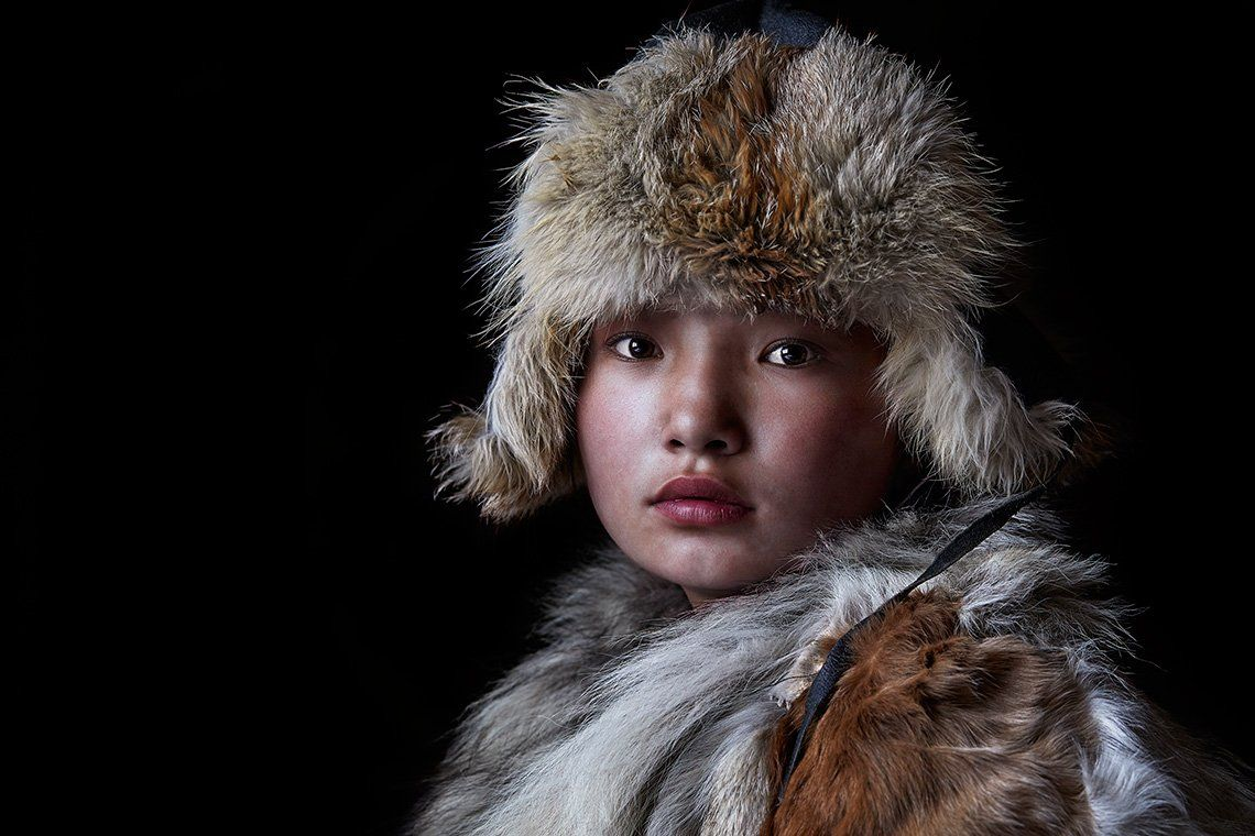 A young Kazakh girl wearing traditional fur coat and hat