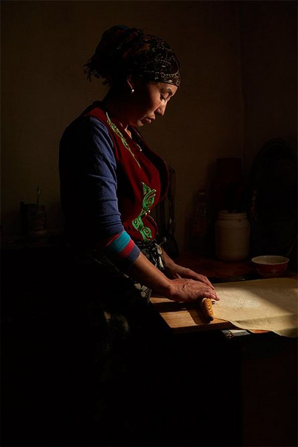 A Kazakh woman rolls out pastry with a wooden rolling pin in a darkened room with light coming from one side