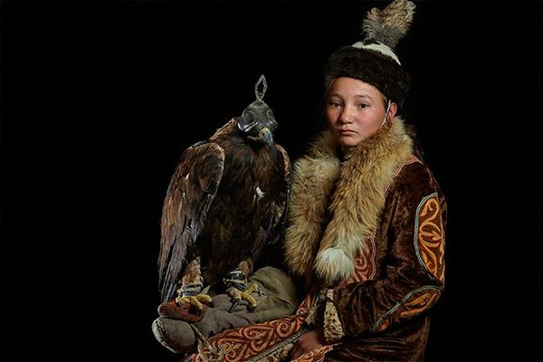 A young Kazakh boy wearing traditional clothing, with a fur collar and warm hat, sits with a hooded Golden Eagle on his arm