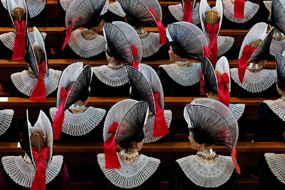 View from above of religious women in ornate costumes, sitting in church pews.