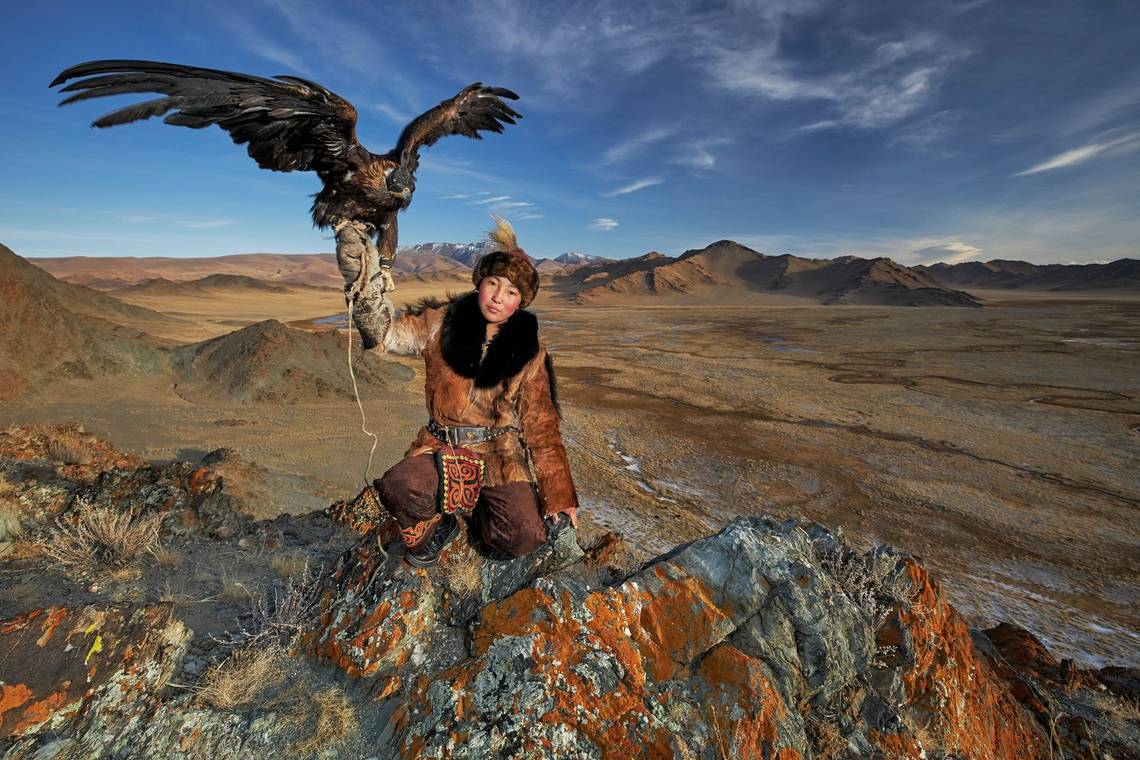 A teenage Mongolian eagle huntress crouches on rocks holding an eagle aloft. Taken by Alessandra Meniconzi on a Canon EOS R.
