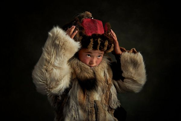 A Mongolian child in a fur coat adjusting her hat with both hands. Taken by Alessandra Meniconzi on a Canon EOS R.
