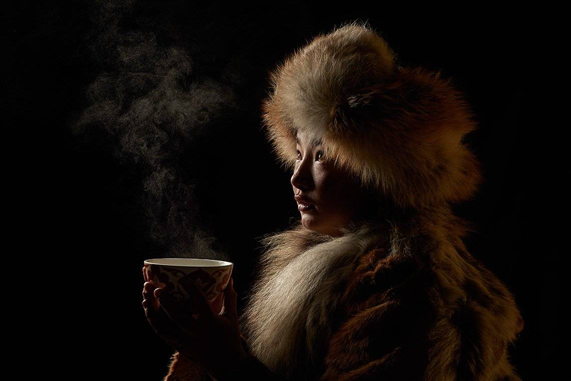 Dim light falls on the raised face of Damel, a 13-year-old Kazakh girl wrapped in a heavy fur coat and headdress, as she looks out of shot, with wisps of steam rising from the cup of tea she is holding in both hands.