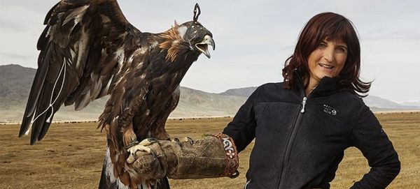 Photographer Alessandra Meniconzi wears a falconry glove and holds an eagle, amid a mountainous landscape.