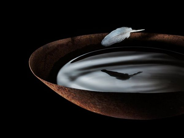 A feather hovers above a wok full of liquid, photographed by Eberhard Schuy on a Canon EOS 5D Mark II.