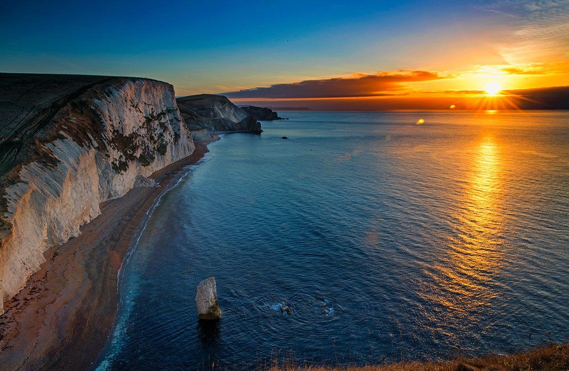 The sun setting over sea, lighting up white cliffs, photographed by Marc Aspland on a Canon EOS-1D X Mark II.