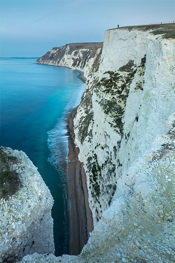 White cliffs seen from above stretching down to the beach. They look bluish-white and have a tiny figure on top in the distance. Photo by David Noton.