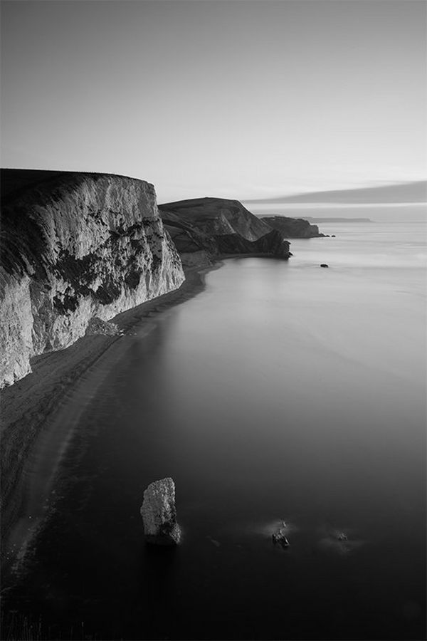 A black and white beach landscape, with rock stacks in the sea and cliffs behind, photographed by Helen Bartlett.