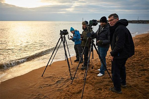 Helen Bartlett, David Noton, Sanjay Jogia and Eddie Keogh taking photographs on the beach at dusk.