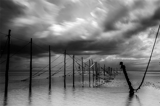A black and white landscape photograph of a seascape by sports photographer Marc Aspland.