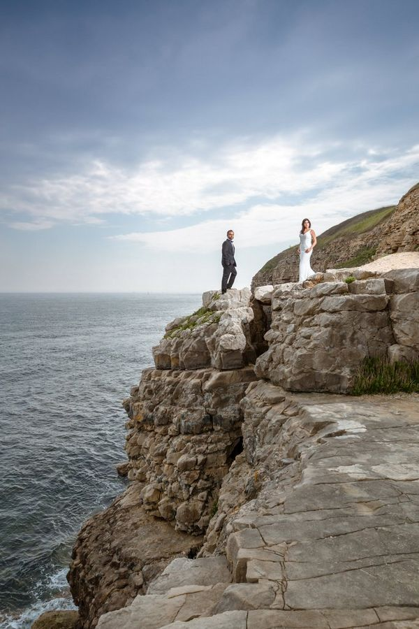 A bride and groom stand on a coastal path, photographed from below by Sanjay Jogia.