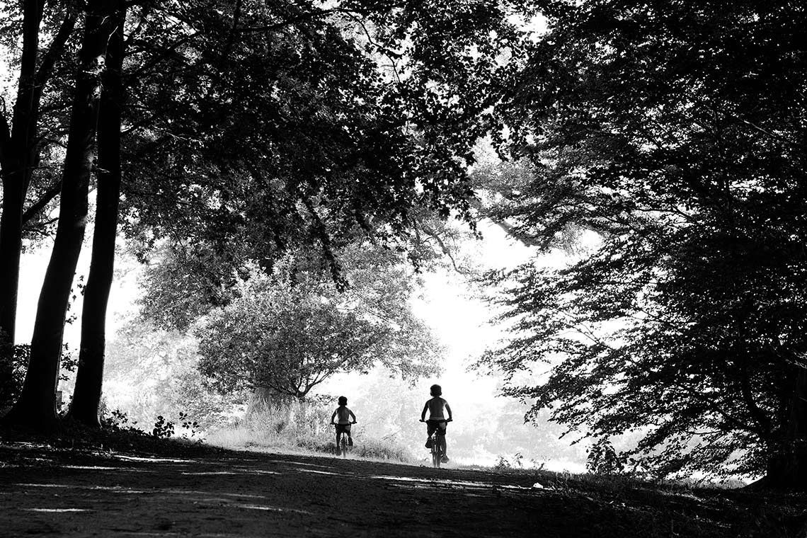 Canon Ambassador Helen Bartlett's black and white image of two children riding bikes beneath large trees.