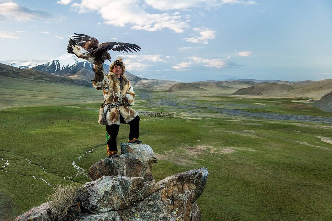 A Kazakh man holding an eagle in front of a mountain landscape. Photo by Joel Santos on a Canon EOS 5DS R.