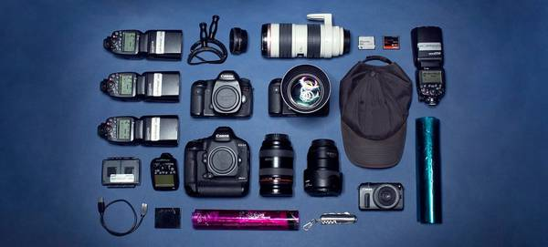 Contents of photographer Jörg Kyas's kitbag, including cameras, lenses, cap and torches.