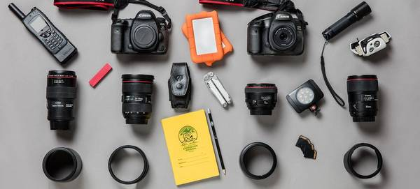 The contents of Paolo Verzone's photography kitbag are laid out, showing Canon cameras and lenses.