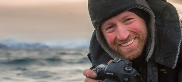 Audun Rikardsen, wearing a warm coat with a hood, holds a Canon camera.